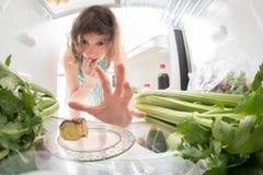 饮食奋斗:充分劫掠从开放冰箱的手一小块甜点绿色 库存照片