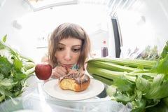 饮食奋斗:充分哀伤地看在冰箱的女孩一个多福饼健康材料里面 免版税库存图片