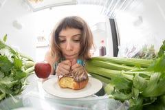 饮食奋斗:充分哀伤地看在冰箱的女孩一个多福饼健康材料里面 免版税图库摄影