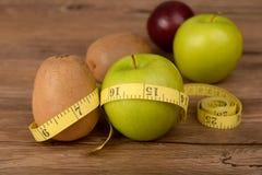 饮食概念、猕猴桃用绿色苹果和测量的磁带 免版税库存图片