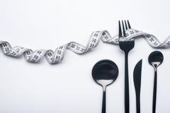 饮食概念、黑叉子和测量的磁带 免版税库存图片