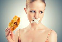 饮食概念。 妇女嘴密封与输送管磁带用小圆面包 库存图片