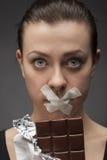 饮食概念:拿着与嘴的妇女巧克力被密封 免版税库存照片
