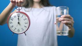 饮食概念 女孩拿着一个闹钟和一杯水 时刻喝水 股票录像