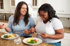 饮食的两名超重妇女吃健康膳食的在厨房里 免版税库存图片