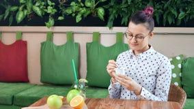 饮食的微笑的偶然少女吃新鲜的酸奶的坐在咖啡馆中景的桌 影视素材