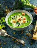 饮食硬花甘蓝光滑的奶油色汤与洒向日葵种子、荷兰芹叶子和油煎方型小面包片在石桌上 免版税库存图片