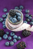饮食膳食。黑莓和蓝莓在一个玻璃瓶子有措施的 免版税库存照片