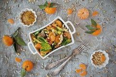 饮食菠菜沙拉和橘子与穿戴芥末和松果 免版税库存照片