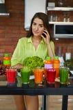 饮食营养 有新鲜的汁液圆滑的人的妇女在厨房里 免版税库存图片