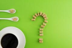 饮食,不健康的甜瘾概念 白色咖啡或茶,两把匙子和红糖立方体当问号 免版税库存图片