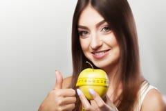 饮食 体育运动 年轻美丽的女孩举行一个苹果和一测量 库存照片