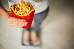 饮食 在拿着不健康的垃圾食品的秤的妇女测量的体重 查出的损失评定躯干重量白人妇女 肥胖病 顶视图 免版税库存图片