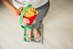 饮食 在拿着不健康的垃圾食品的秤的妇女测量的体重 查出的损失评定躯干重量白人妇女 肥胖病 顶视图 库存图片