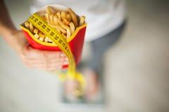 饮食 在拿着不健康的垃圾食品的秤的妇女测量的体重 查出的损失评定躯干重量白人妇女 肥胖病 顶视图 免版税库存照片