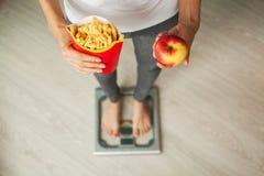饮食 在拿着不健康的垃圾食品的秤的妇女测量的体重 查出的损失评定躯干重量白人妇女 肥胖病 顶视图 库存照片