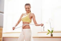 饮食 在背景空白弓概念节食的显示评定编号附近自己的缩放比例磁带文本附加的空白视窗包裹了您 测量她的腰部的运动服的妇女 免版税库存图片