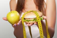 饮食 有害和有用的食物 一个女孩做挑选eithe 免版税库存照片