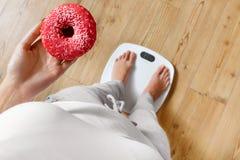 饮食 秤的妇女,拿着多福饼 不健康的食物 Ob 库存图片