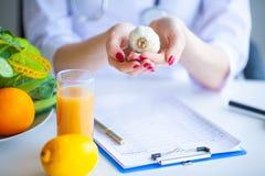 饮食 Nutritionist医生举行大蒜在她的办公室 概念  免版税库存照片