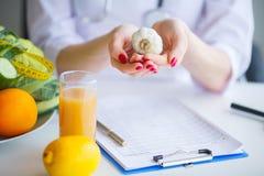 饮食 Nutritionist医生举行大蒜在她的办公室 概念  库存照片