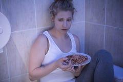 暴饮暴食的哀伤的女孩 免版税库存图片
