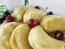 饺子手工制造开胃菜酥皮点心午餐在白色木背景的一棵樱桃 免版税库存图片