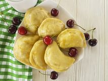 饺子手工制造开胃菜酥皮点心早餐午餐在白色木背景的一棵樱桃 免版税图库摄影