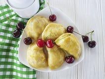 饺子手工制造开胃菜酥皮点心食家早餐午餐在白色木背景的一棵樱桃 免版税库存照片