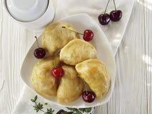 饺子手工制造面团开胃菜酥皮点心点心土气食家早餐午餐在白色木背景的一棵樱桃 免版税库存照片