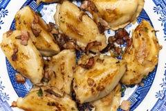 饺子` pierogi `服务用葱和烟肉 库存图片