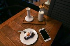 饼和叉子在板材、电话和牛奶瓶在whi 库存图片