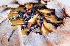 饼干用桃子和蓝莓在一张白色桌上 免版税库存图片