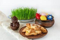 饼干,甜巧克力小鸡新鲜的绿草上色了在复活节歌曲的鸡蛋 免版税库存图片