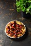 饼烘烤了用草莓,有薄荷叶的一个碗在黑暗的背景 库存照片