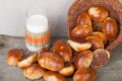 饼用肉或圆白菜在一个柳条筐和一杯牛奶 库存照片