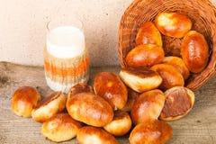 饼用肉或圆白菜在一个柳条筐和一杯牛奶 免版税库存图片