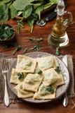 馄饨用菠菜和乳清干酪乳酪 巴马干酪和油 在板材 图库摄影