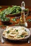 馄饨用菠菜和乳清干酪乳酪 巴马干酪和油 在板材 免版税图库摄影