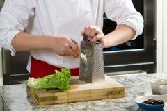 首席厨师磨碎在木桌上的辣根 库存照片
