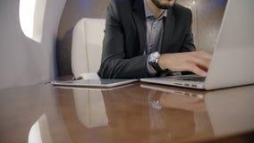 首席在他的膝上型计算机和读书新闻的银行家主任男性polititian文字新闻发布在私人喷气式飞机的片剂 股票录像