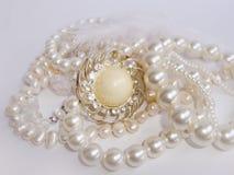 首饰、珍珠项链和别针 免版税库存图片