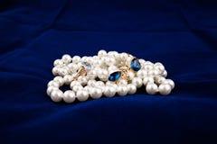 首饰。成珠状小珠、蓝色耳环和一只金戒指与黄玉 库存图片