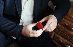 首饰的红色皮革箱子在人` s手上 特写镜头 严密的黑衣服和白色衬衣 免版税库存图片