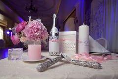 香宾、蜡烛和花当婚礼装饰 切开蛋糕的刀片和刀子 免版税库存图片