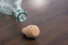 香宾在木桌上的瓶黄柏 免版税库存图片