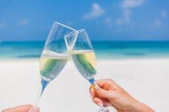 香宾玻璃在海滩背景的手上 浪漫蜜月背景 免版税库存图片