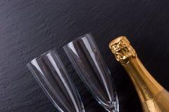 香宾瓶和两块香槟玻璃在黑板岩板材 图库摄影