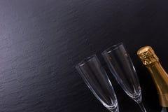 香宾瓶和两块香槟玻璃在黑板岩板材 免版税库存照片