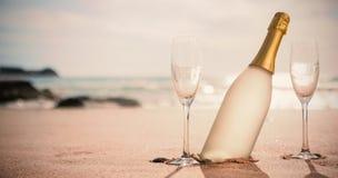 香宾瓶和两块玻璃在沙子 免版税库存图片